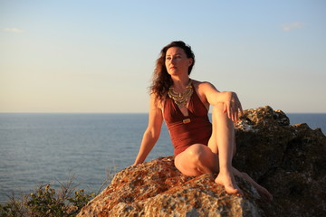 A beautiful young woman with long hair and a swimsuit with ornaments sunbathes on a rock against the sea during sunset.