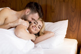 Beautiful young loving couple lying in bed - 213983660