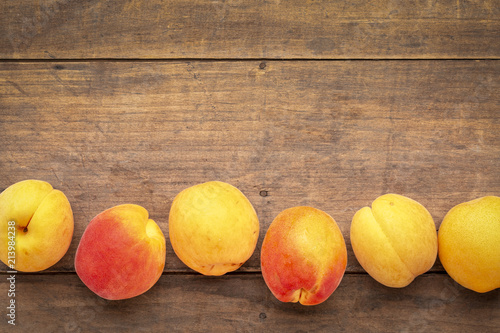 fresh ripe apricots on a rustic wood - 213984238