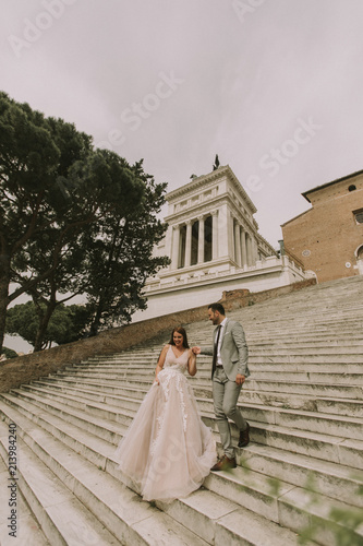 Bride and groom walking outdoors at Spagna Square and Trinita' dei Monti in Rome, Italy - 213984240