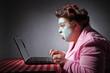Leinwandbild Motiv femme ronde drôle en peignoir et bigoudis devant son ordinateur portable