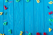 top view of colorful various numbers and paper clips on blue wooden background