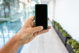 Close up of mobile phone with corporate environment blurred in the background. - 213997818