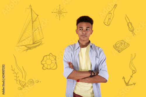 Foto Murales Curious person. Curious handsome student smiling and standing with his arms crossed while dreaming about experiencing sea adventures