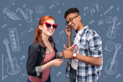 Great sound. Positive young couple feeling relaxed while wearing convenient earphones and listening to music - 214007445