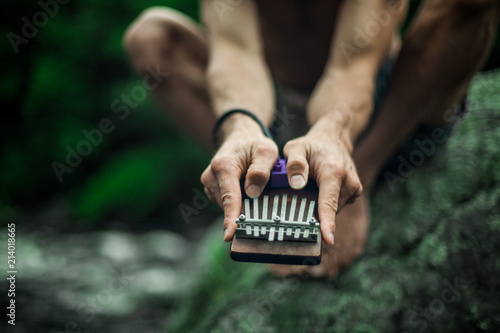 Close up of a man's hands playing with a little kalimba in front of a river - 214018665