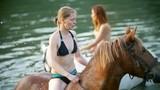 Happy young women ride on horse on the river in water - 214060456