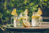 Detox water with lemon and mint in jars on the garden table. Selective focus.