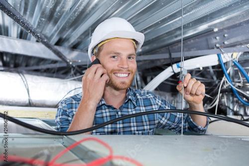 Leinwandbild Motiv cheerful smiling builder working in the ceiling