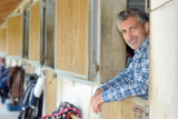 Man leaning over stable door - 214071261