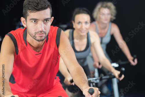 Poster group in the gym on the stationary bikes