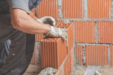 Real construction worker bricklaying the wall indoors. - 214073469