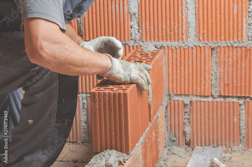 Fototapeta Real construction worker bricklaying the wall indoors.