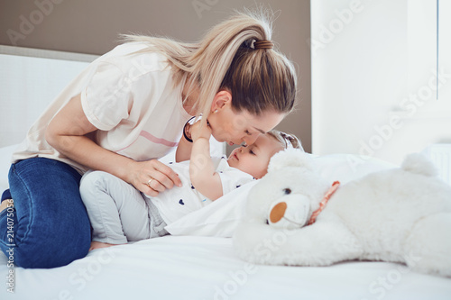 Foto Murales Mother with baby lying on the bed in a white room.