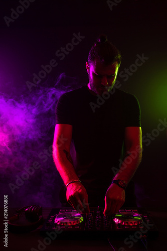 Attractive young DJ playing on turntables with color light effects - 214076880
