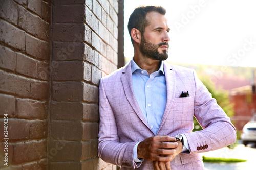 Leinwandbild Motiv Portrait of sexy handsome fashion businessman model dressed in elegant suit posing near brick wall on the street background. Metrosexual