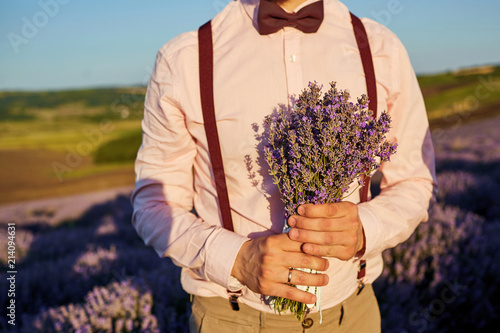 Close-up of a bouquet of lavender in the hands of the groom in the field of lavender. - 214094631