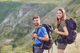 Happy couple of tourists with backpacks smiling in nature. - 214099007