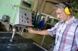 Leinwandbild Motiv worker tending to a machine