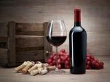 Weinflasche mit Korken, Trauben, Glas Wein, Weinkiste auf Holztisch mit Holzhintergrund - 214102247