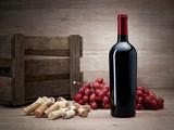 Weinflasche mit Korken, Trauben und Weinkiste  auf Holztisch mit Holzhintergrund - 214102471