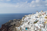 Whitewashed Houses and Windmill on Cliffs with Sea View in Oia, Santorini, Cyclades, Greece - 214105653