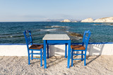Table and chairs standing on the coast of Aegean sea in Greek island of Milos - 214111264