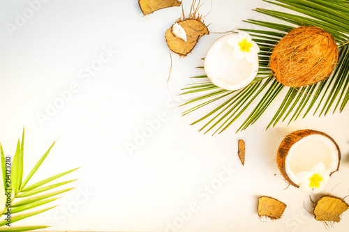 Summer flat lay scene with palm leaves and flowers with coconut fruits on wooden background with copy space, retro toned