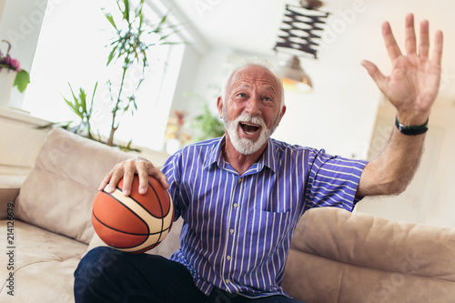 Fotobehang Basketbal Senior man cheering for a basketball game and holding a basketball ball