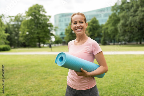 Foto Murales fitness, sport and healthy lifestyle concept - happy smiling woman with exercise mat at park