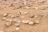 Pointed stones on sand. Sand and stone background - 214144220