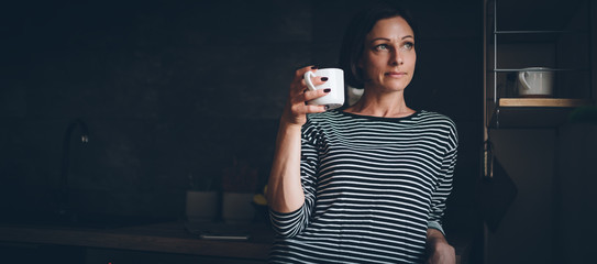 Woman standing in the kitchen and drinking coffee © kerkezz