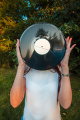 Girl holding a vinyl record in her hands, covering her face