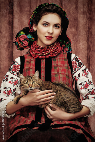 Three quarter isolated portrait of a young Slavic woman in ethnic costume, wearing embroidered blouse, floral head scarf, red bead necklace, holding a cat on her lap, posing on dark brown background. © RedUmbrella&Donkey