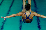 Female diver jumping into the pool - 214213684
