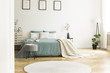 White round rug in front of green bed with blanket in bedroom interior with posters. Real photo