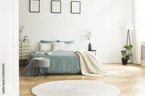 Biały okrągły dywanik przed zielonym łóżku z kocem w sypialni wnętrze z plakatów. Prawdziwe zdjęcie