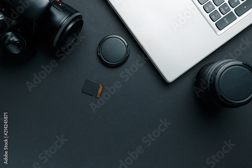 Work space on black table of photographer. Minimal workspace with Laptop, camera and lens copy space on dark background. Modern and elegant. Top view. Flat lay style.