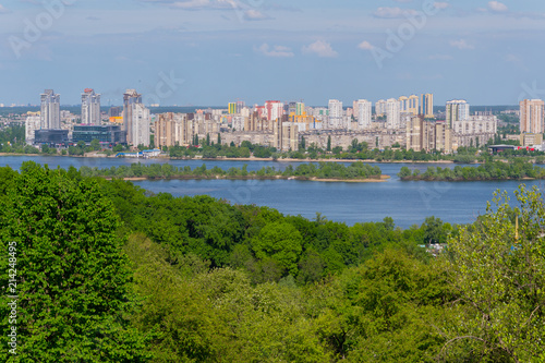 Canvas Kiev Panorama of multi-storey buildings on the shore of the Dnipro River under the blue sky. Kiev. Ukraine
