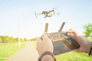Flying quadcopter drone with Action Camera in the air under blue sky and remote control in the hands