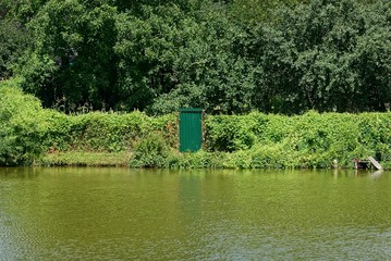 covered with green vegetation fence and closed door on the shore of the reservoir