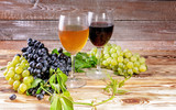 Red and white wine in a glass. White and red grapes on a wooden background. - 214315228
