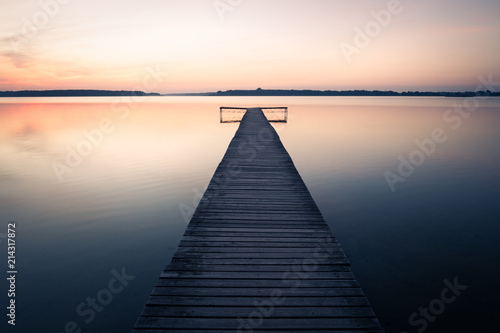 Acrylglas Pier Old empty wooden jetty on lake, during sunrise.