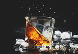Whiskey with ice, splashes out of glass, dark background, toned image, selective focus - 214319639