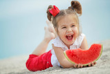 Child with a watermelon at sea  - 214336836