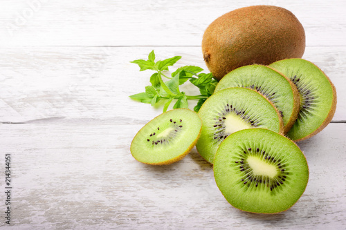 Foto Murales Green kiwi and mint leaves on white wood background with space for text