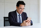 Asian Businessman holding smart phone with happy smiling face inside eco office building background, businessman on smart phone - 214356653
