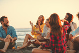 Happy friends sitting on the beach singing and playing guitar during the sunset - 214368481