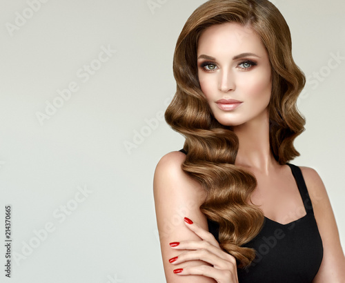 Brunette brown girl with long  and   shiny curly hair .  Beautiful  model woman  with curly hairstyle. Care , cosmetic and beauty