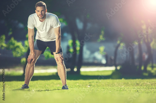 Leinwandbild Motiv Full length portrait of focused sportsman training in park. He is bending forward and putting hands on knees with concentration. Copy space in right side